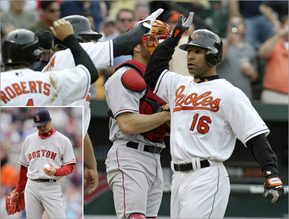 Baltimore Orioles' Jay Payton (16) is greeted at home plate by teammates Freddie Bynum and Brian Roberts (1) after hitting a grand slam home run off of Boston Red Sox relief pitcher Hideki Okajima (below left) in the seventh inning of their MLB American League baseball game in Baltimore, Maryland May 14, 2008