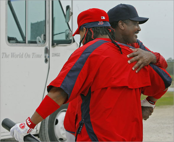 An ironic phrase is seen in the backround at left on a FedEx truck that just happened to be driving by as Red Sox leftfielder Manny Ramirez, (left), gets a hug from another legendary Boston leftfielder, Jim Rice (right)