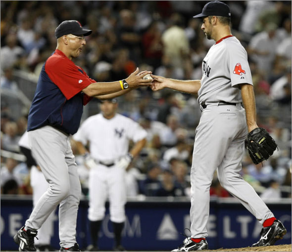 Boston Red Sox manager Terry Francona, left, takes the ball from pitcher John Smoltz after Smoltz gave up a three-run home run to New York Yankees' Melky Cabrera in a baseball game at Yankee Stadium in New York, Thursday, Aug. 6, 2009.