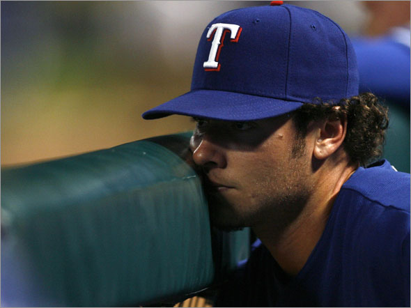Rangers' Jarrod Saltalamacchia watches from the dugout as the Toronto Blue Jays score a run in the ninth inning of their MLB American League baseball game in Arlington, Texas August 31, 2009.