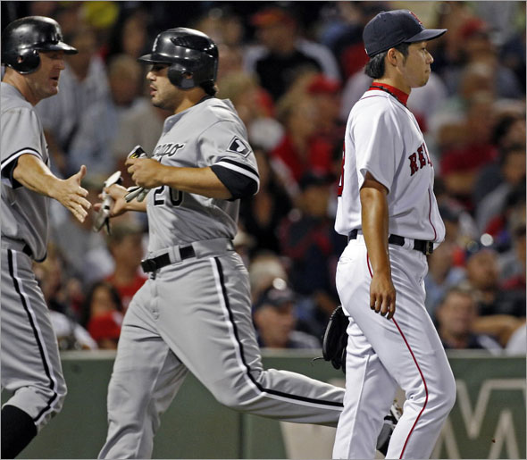 Red Sox starting pitcher Junichi Tazawa (who was backing up the plate) doesn't join in the hand slapping of the White Sox Jim Thome (left) and Carlos Quentin (center) who have both just scored on a wall scraping double by number nine hitting teammate Jayson Nix in the second inning.