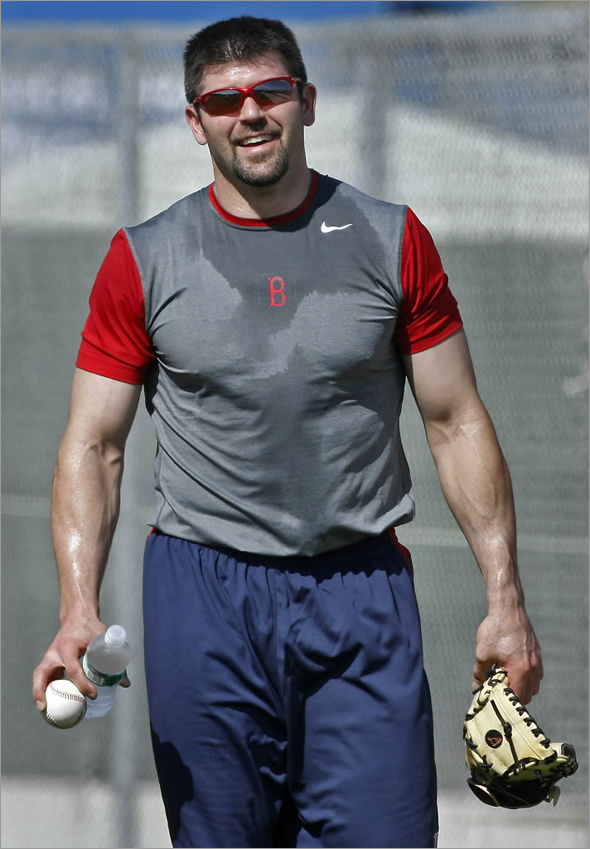 Red Sox captain Jason Varitek arrived in camp today, just in time to take part in the team's conditioning drills that they put players through at the beginning of the season. He is shown leaving the field after the drills, drenched in sweat.