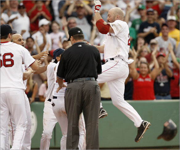 Red Sox's Kevin Youkilis jumps into his teammates waiting at home plate after his two-run walk off home run during the bottom of the 13th inning of their 5-3 win over the St. Louis Cardinals in a baseball game at Fenway Park in Boston, Sunday, June 22,  2008