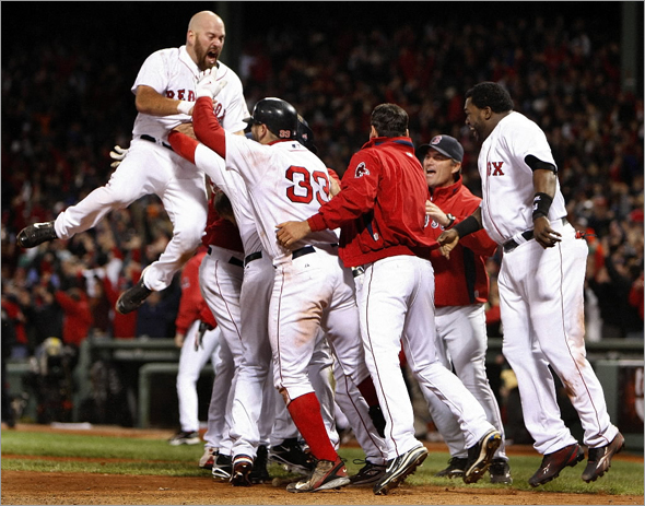 Kevin Youkillis leaps onto Jason Bay and the celebrating Red Sox after they clinched the Division series