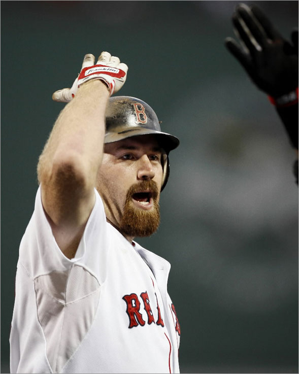 Kevin Youkilis is greeted at home plate by a teammate after the first of his pair of two- run home runs against the Oakland Athletics, during Boston's 12-2 win in a baseball game at Fenway Park in Boston on Saturday, Aug. 2, 2008.