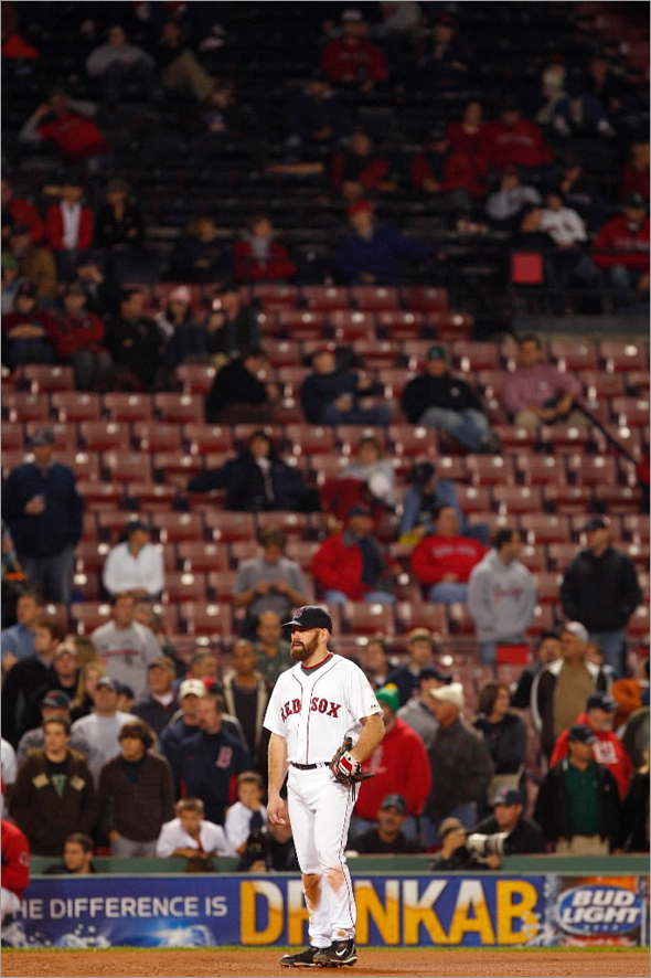 Kevin Youkilis #20 of the Boston Red Sox looks on as the stands are seen nearly empty during game four of the American League Championship Series against the Tampa Bay Rays during the 2008 MLB playoffs at Fenway Park on October 14, 2008 in Boston, Massachusetts.