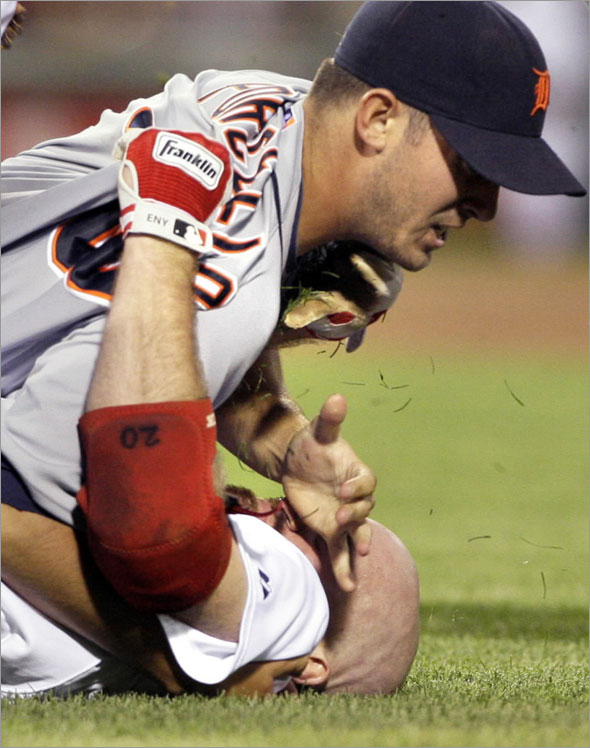 Boston Red Sox's Kevin Youkilis, below, wrestles with Detroit Tigers starter Rick Porcello after being hit by a pitch in the second inning of their baseball game at Fenway Park in Boston, Tuesday, Aug. 11, 2009.
