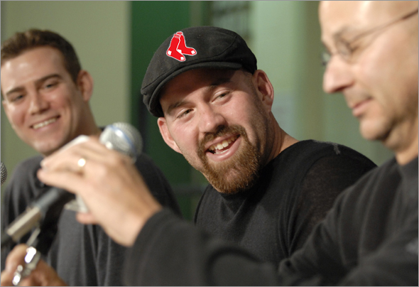 Kevin Youkilis responds to a question during a Red Sox press conference announcing an agreement to terms on a 4 year contract with the first baseman. Red Sox manager Terry Francona is seen at far right.