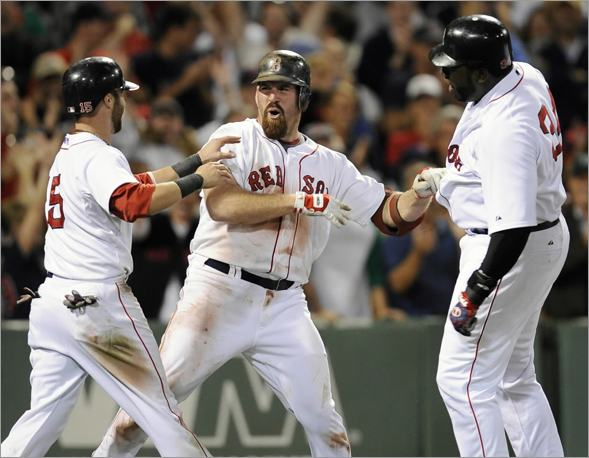 Kevin Youkilis is congratulated by teammates David Ortiz and Dustin Pedroia after Youkilis hit a game-winning home run during the 8th inning. The Boston Red Sox host the Texas Rangers in an MLB game played at Fenway Park in Boston, MA Tuesday, August 12, 2008