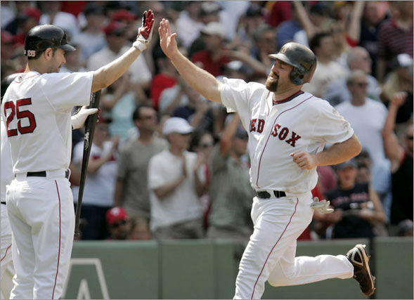 Kevin Youkilis, right, is welcomed to home plate by Mike Lowell as Youkilis scores on a double by Manny Ramirez in the fifth inning of a baseball game against the Minnesota Twins at Fenway Park in Boston on Wednesday, July 9, 2008
