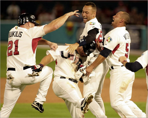 Team USA's David Wright is congratulated by Kevin Youkilis, Derek Jeter, second from right, and Shane Victorino after a 6-5 win over Puerto Rico at the World Classic Baseball game in Miami, Tuesday, March 17, 2009.