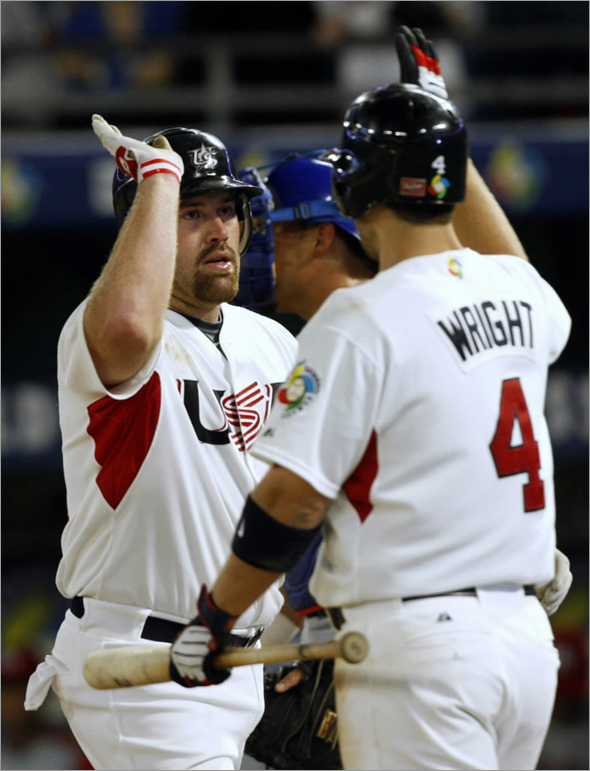 Team USA's Kevin Youkilis is congratulated by teammate David Wright after he hit a third inning home run against Team Puerto Rico during their second round World Baseball Classic game in Miami, Florida, March 17, 2009.