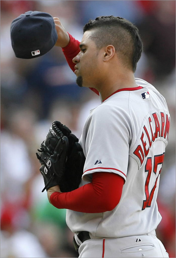 Red Sox pitcher Manny Delcarmen wipes his head after giving up a double to Los Angeles Angels' Casey Kotchman allowing Howie Kendrick and Chone Figgins to score during the eighth inning of their MLB American League baseball game in Anaheim