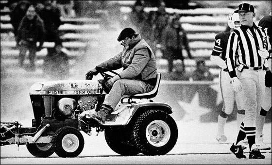 Mark Henderson, 24, a convict on work release from the Massachusetts Correctional Insitution at Norfolk, Mass, clears snow Dec. 12, 1982 at Schaefer Stadium, Foxboro,Mass. Referee Bob Frederic looks on during a third quarter break in action between the New England Patriots and Miami Dolphins.