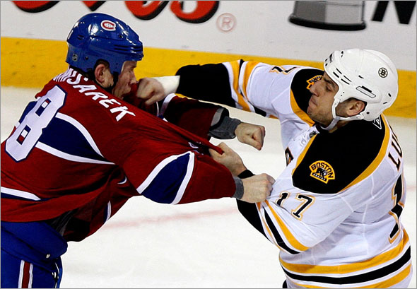 Boston Bruins left wing Milan Lucic  connects with a right to the face of Montreal Canadiens defenseman Mike Komisarek during a fight late in the 2nd period.