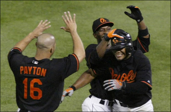 Baltimore Orioles' Melvin Mora is greeted by teammates Freddie Bynum and Jay Payton after bunting in the winning run against the New York Yankees in the 10th inning of their MLB American League baseball game in Baltimore,