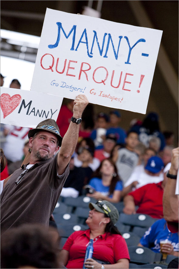 Jeff Turcotte, of Albuquerque, N.M., holds up a greeting for Los Angeles Dodgers' Manny Ramirez while Ramirez was playing for the Dodgers' Triple-A baseball team, the Albuquerque Isotopes, against the Nashville Sounds in Albuquerque