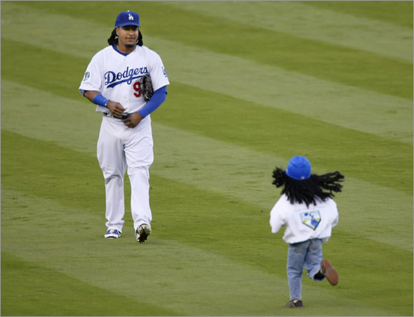 A fan runs out to get an autograph from Los Angeles Dodgers' Manny Ramirez during pre-game activities before Game 4 of Major League Baseball's NLCS playoff series in Los Angeles October 13, 2008.