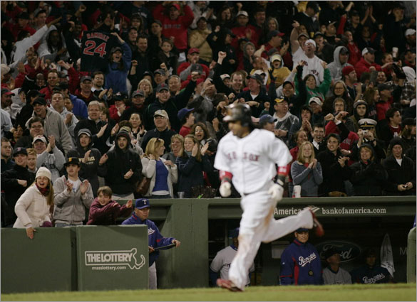 Fans cheer as Boston's Manny Ramirez  heads to home plate after a two run blast to give the Red Sox the lead against Texas during the 8th inning of Saturday's game at Fenway Park