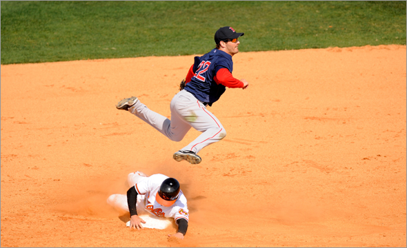 Nick Green of the Boston Red Sox leaps over Ryan Freel of the Baltimore Orioles trying to turn a double play during a spring training game at Fort Lauderdale Stadium on March 2, 2009 in Fort Lauderdale, Florida.