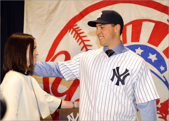 New York Yankees first baseman Mark Teixeira looks at his wife Leigh at a news conference after signing as a free agent with the team at Yankee Stadium in New York, January 6, 2009.