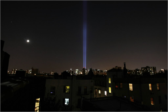 The Tribute in Light is seen during a test run as the moon rises over the East Village with Lower Manhattan in the background September 8, 2008 in New York City.