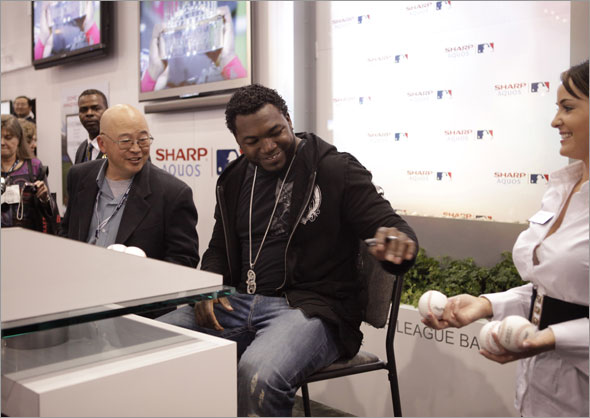 David Ortiz, center, signs autographs at the Sharp booth at the International Consumer Electronics Show (CES) in Las Vegas,Thursday, Jan. 8, 2009.