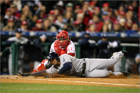 Jason Bartlett of the Tampa Bay Rays is tagged out at home plate by catcher Carlos Ruiz of the Philadelphia Phillies to end the top of the seventh inning during the continuation of game five of the 2008 MLB World Series on October 29, 2008 at Citizens Bank Park in Philadelphia, Pennsylvania.