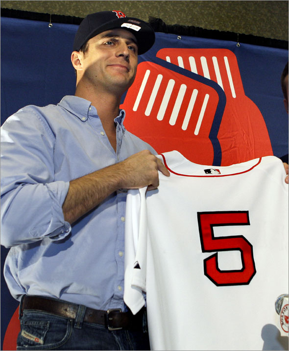 Newly acquired Boston Red Sox Rocco Baldelli holds up his new number 5 Red Sox jersey during a news conference in Boston on Thursday, Jan. 8, 2009.