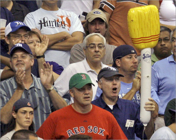 Rays fan celebrates with an inflatable broom next to a Boston Red Sox fan following the Rays 7-6 win during a baseball game Wednesday, July 2, 2008, in St. Petersburg, Fla. The Rays swept a three-game series from the Red Sox.