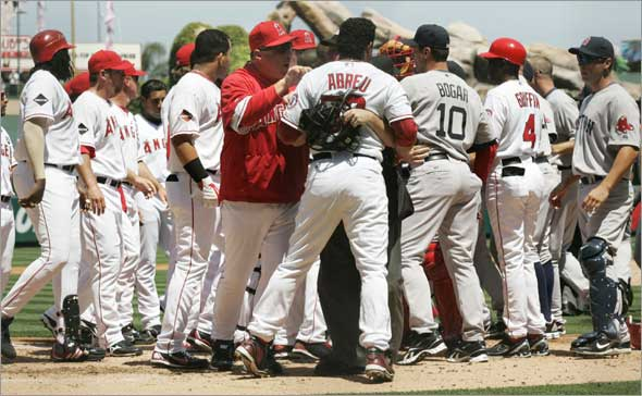 Bobby Abreu is held back by the umpire and Angels manager Mike Scioscia as the benches clear after Boston Red Sox's Josh Beckett threw a high pitch that hit the backstop during the first inning of a baseball game Sunday, April 12, 2009, in Anaheim, Calif.
