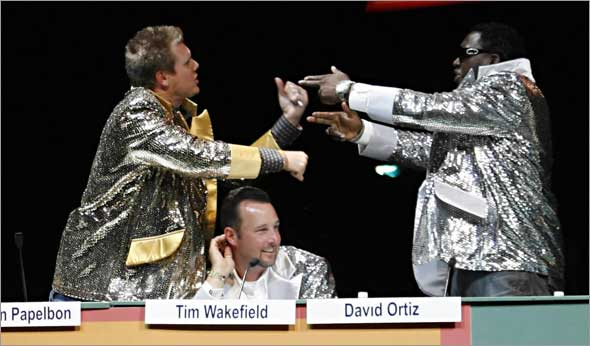 Red Sox pitcher Jonathan Papelbon, left, and designated hitter David Ortiz, right, have a mock argument above pitcher Tim Wakefield, center, during a game show spoof at the 2009 Red Sox Foundation Welcome Home Dinner