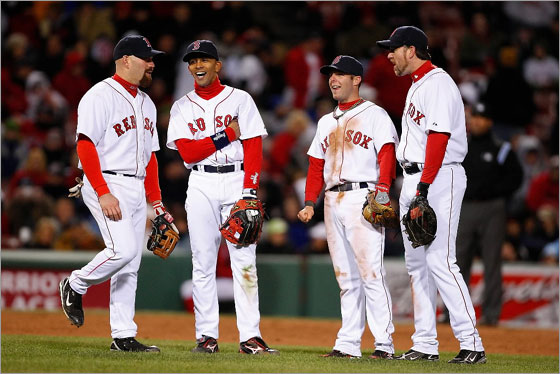 Kevin Youkilis, Julio Lugo, Dustin Pedroia, and Sean Casey  of the Red Sox share a laugh during a game against the New York Yankees at Fenway Park on April 13, 2008 in Boston, Massachusetts.