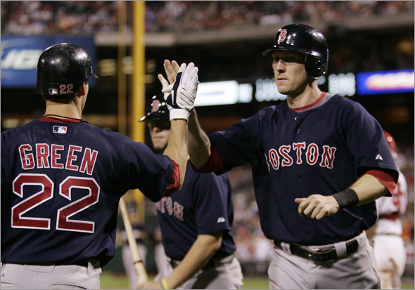Boston Red Sox' Nick Green, left, hi-fives Jason Bay, right, who scored the winning run on a single by Jacoby Ellsbury in the 13th inning of an interleague baseball game Friday, June 12, 2009, in Philadelphia.