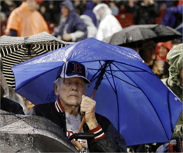 Eighty-year-old Dick Emerson of Haverhill, Mass. closes his eyes during a rain delay in the top of the first inning of a baseball game between the Boston Red Sox and the Tampa Bay Rays at Fenway Park in Boston Friday, Sept. 11, 2009.