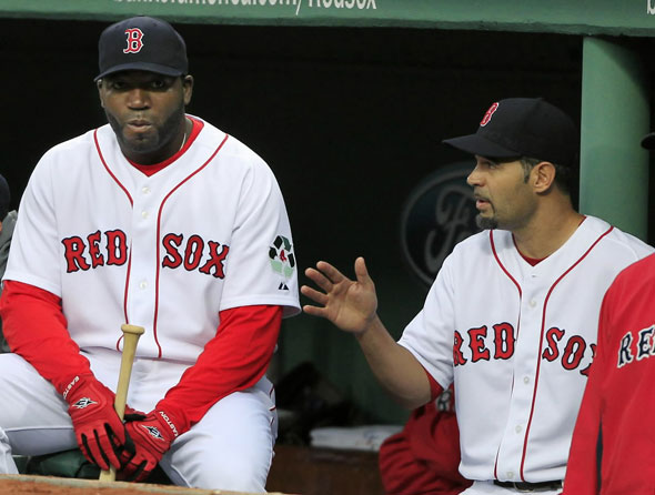 Red Sox designated hitter David Ortiz, left, sits on the bench and listens to teammate Mike Lowell, who replaced Ortiz in the line up as DH, during the first inning against the Texas Rangers in a baseball game at Fenway Park in Boston,