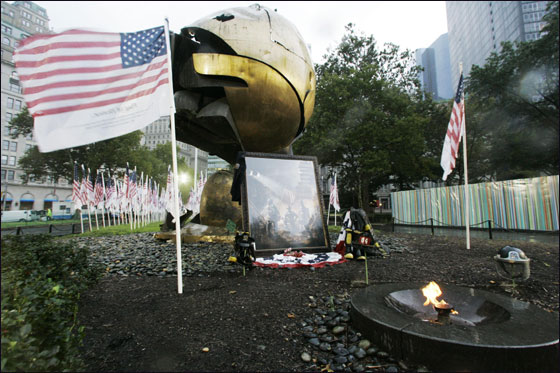 An American flag inscribed with the names of the victims of the Sept. 11 attacks flies at the 9/11 memorial field near the eternal flame and the globe saved from the World Trade Center Site on the  sixth anniversary of the terrorists attacks on the World Trade Center, Tuesday, Sept. 11, 2007, in New York.