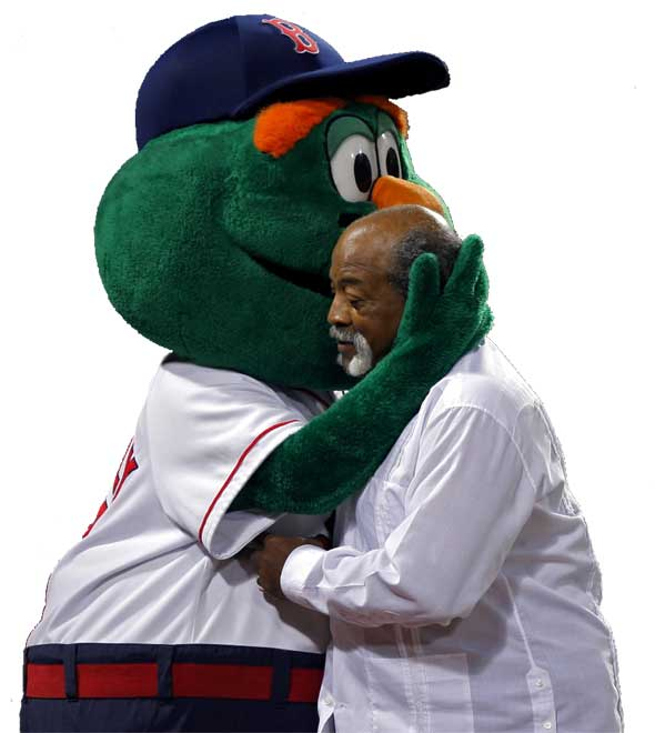 Red Sox lergend Luis Tiant gets a hug from outgoing mascot Wally the Green Monster