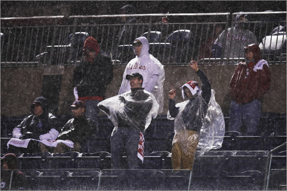 Fans watch the sixth inning in the pouring rain during Game 5 of the baseball World Series between the Philadelphia Phillies and Tampa Bay Rays in Philadelphia, Monday, Oct. 27, 2008.