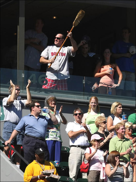 A fan of the Boston Red Sox holds a broom in the suite level as the Red Sox sweep a four game series from the Chicago White Sox on August 26, 2007 at US Cellular Field in Chicago, Illinois.