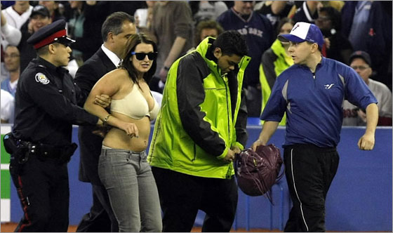 A woman who ran onto the field is arrested and escorted off the field by police in the ninth inning of the Toronto Blue Jays game against the Boston Red Sox at the Blue Jays' home-opener at the Rogers Centre April 4, 2008 in Toronto, Ontario, Canada. g