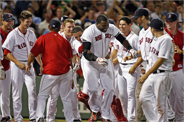 David Ortiz is mobbed at the plate after his game winning home run.The Boston Red Sox play the Chicago White Sox at Fenway Park.