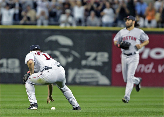 As the bleacher fans cheer in the backround, Red Sox 2B Tony Graffanino retrieves the ball he has just missed for a fifth inning error. CF Johnny Damon comes in at right.