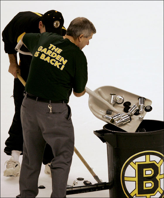 Workers clear mini replicas of the Stanley Cup, a fan appreciation gift, which were thrown on the ice by fans following a Montreal Canadiens goal in the final minute of a game against the Boston Bruins in Boston, Wednesday Oct. 5, 2005.  The Canadiens beat the Bruins 2-1.