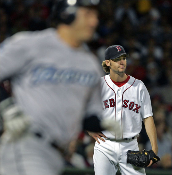 Red Sox starter Bronson Arroyo (right) watches as a third inning home run off the bat of Toronto's Frank Catalanotto (left) sails out of the park.