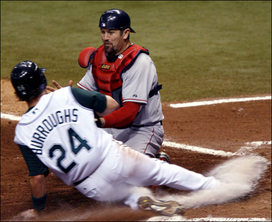 Sean Burroughs of the Tampa Bay Devil Rays slides into home safely where Catcher Jason Varitek of the Boston Red Sox missed the tag April 28, 2006 at Tropicana Field in St. Petersburg, Florida.