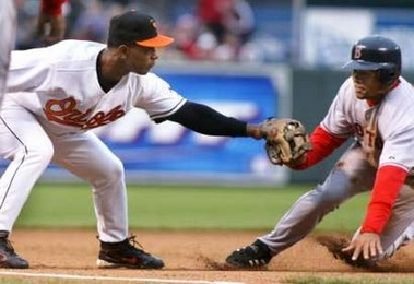 Baltimore Orioles third baseman Melvin Mora (L) tags out Boston Red Sox base runner Coco Crisp who was trying to steal third base in the third inning of their game at Camden Yards in Baltimore, Maryland April 8, 2006.
