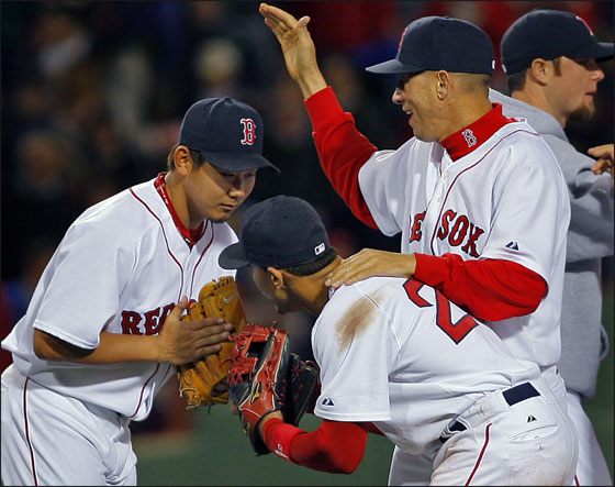 Red Sox pitcher Daisuke Matsuzaka exchanges bows with SS Julio Lugo, while at the same time getting a pat on the back from Julian Tavarez following his complete game 7-1 victory over the Detroit Tigers at Fenway Park.