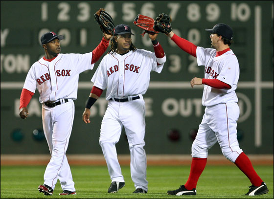 Red Sox outfielders (left to right) Willie Harris, Manny Ramirez, and Trot Nixon high five after the final out of Boston's 9-5 victory over the Yankees at Fenway Park. Globe Staff Photo/Jim Davis