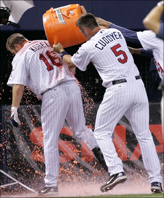 Minnesota Twins' Michael Cuddyer (5) dumps a bucket of Gatorade on teammate Jason Kubel after Kuble hit a grand slam in the 12th inning to beat the Boston Red Sox 5-2 in a baseball game in Minneapolis, Tuesday